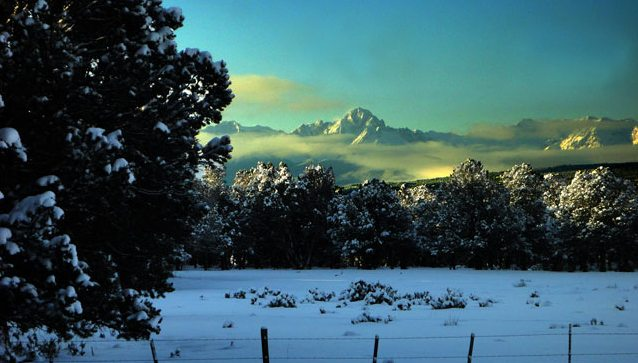 Snow on the ground all winter! That's Mt. Sneffels with the early-morning low clouds surrounding it.